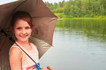 lost lake: Pretty little girl waiting for the rain in cloudy day, holding an umbrella, standing by the lake Stock Photo