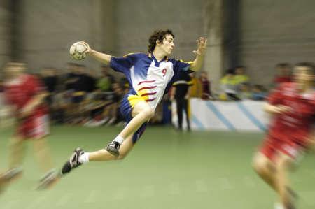 balonmano: jugador joven del balonmano en un f�sforo que salta para anotar una meta Foto de archivo
