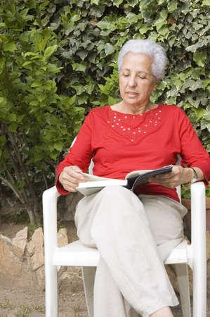 Senior lady reading in her garden Stock Photo - 913162