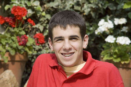 Happy teenager with braces on teeth in the garden photo