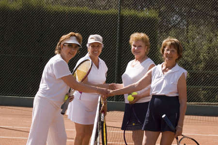 70s tennis: Senior women shaking hands after tennis match Stock Photo