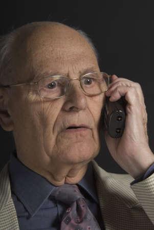 distinguished: Senior distinguished businessman talking on the phone over dark background
