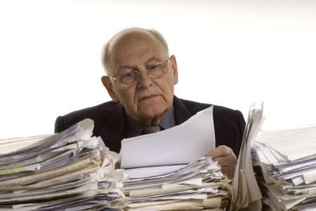 Uomo d'affari con la tabella completa dei fascicoli  Archivio Fotografico