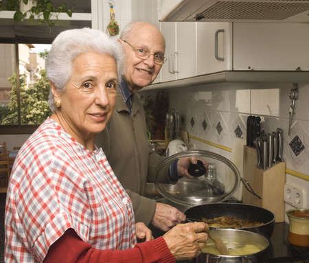 Happy senior couple cooking at home photo