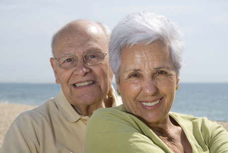 Senior smiling couple with sea in the background. photo