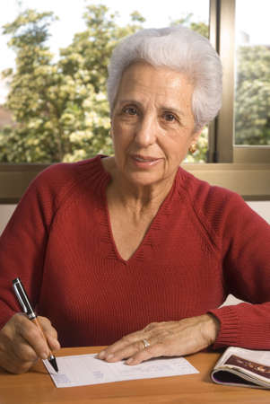 Portrait of a senior lady writing at home Stock Photo - 2954400