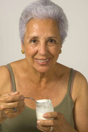 75s: A beautiful seventy five year old woman eating a yogurt after doing exercise. Stock Photo
