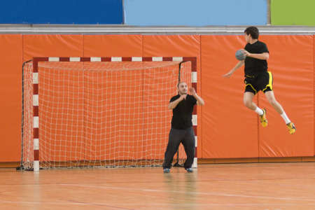 handball: handball player jumping with the ball, trying to score a goal Stock Photo