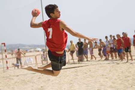 pallamano: Pallamano giocatore che salta con la palla cercando di segnare un gol in una partita di pallamano spiaggia Archivio Fotografico