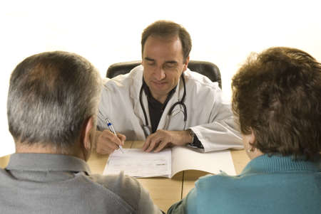 medical practice: Senior couple at doctors consultation on white background