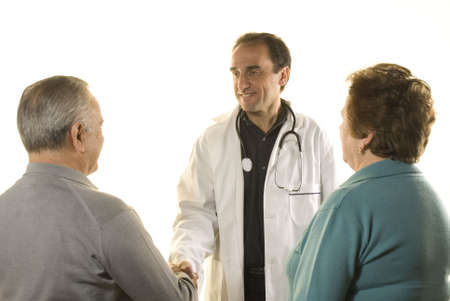 Senior couple at doctor's consultation on white background photo