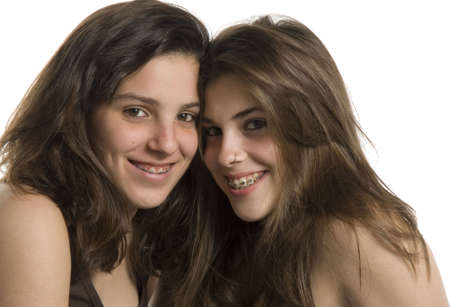 Two adolescent girls on a studio shot on white background photo