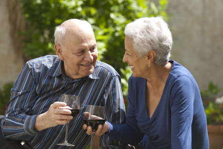 Lovely senior couple on a picnic toasting with wine photo