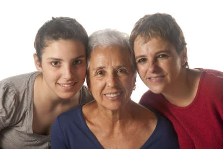 75s: grandmother with adult daughter and granddaughter embracing and looking at camera