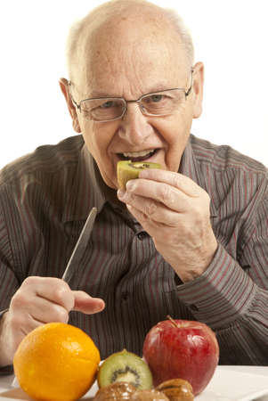 Senior man eating fresh fruit photo