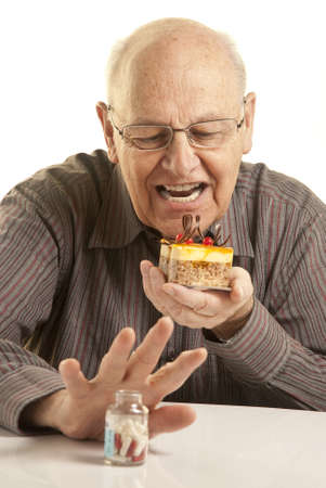 Senior man eating a cake while hiding a bottle of pills photo