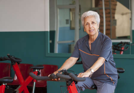 Senior woman exercising on spinning bicycle photo