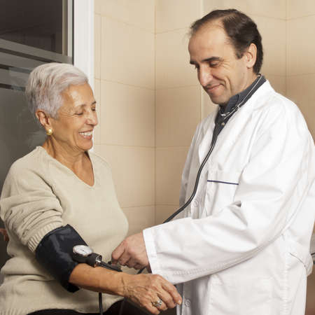 Male doctor measuring blood pressure of senior female patient at hospital photo
