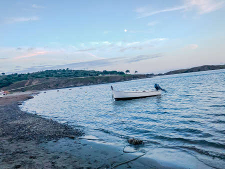 Long shot of a landscape of a beach where a boat is moored in a sunset of a bright day in Cadaques, Barcelona, Catalonia, Spain.