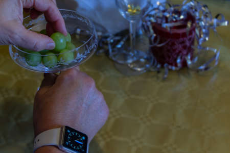 Close up. Hands having a drink with grapes. on his right wrist you can see a clock about to mark twelve. New Year's Eve concept.