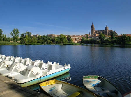 Boats docked on the Tormes river, in Spain, summer, day time, clear sky and river, peaceful scene