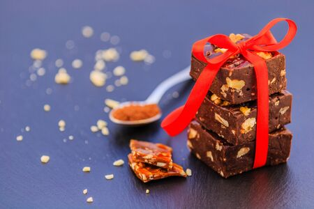 Homemade chocolate and caramel with peanuts and cocoa on a black background. Stock fotó