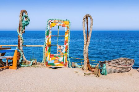 A blue door with colorful glass and anchors on the beach, Vama Veche, Black Sea, Romania. Stock fotó