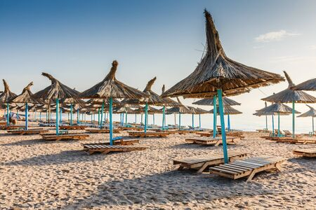 Black Sea, Romania. Straw umbrellas on the beach in Vama Veche village.