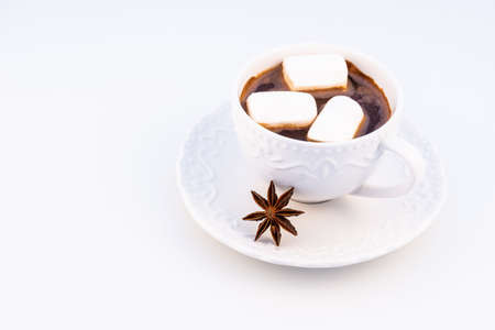Hot chocolate with marshmallow and anasone on a white background, top view.