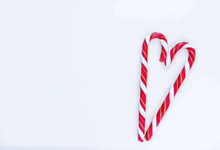 Candy cane in the shape of the heart with white space for text. Flat lay, top view.