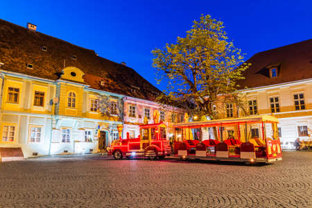 Sighisoara, Romania. Old town square and touristic train.