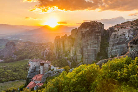 Meteora, Greece. Sandstone rock formations, the Rousanou and Nikolaos monasteries at sunset.