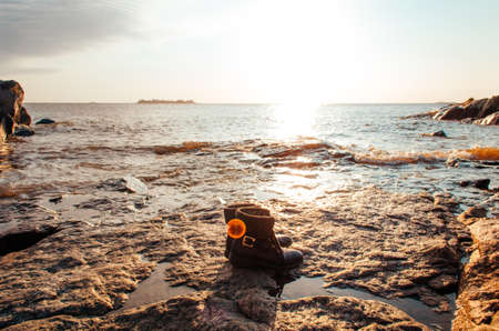 Black feminine travel boots in front of breathtaking view of Rio de La Plata in the golden hour.
