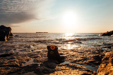 Black feminine travel boots in front of breathtaking view of Rio de La Plata in the golden hour.