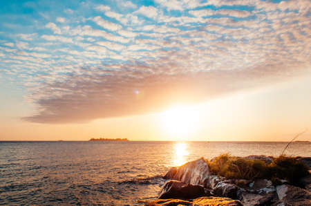 A breathless capture of the golden hour in Colonia Del Sacramento, Uruguay with a view to Rio De La Plata with reflexions of the sunset over the rocks. 版權商用圖片