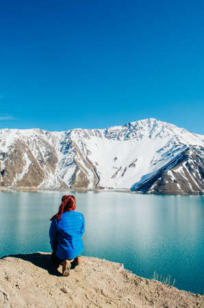 A young adult woman in the dirt road and looking away from the camera enjoying the view of El Yeso Dam in the Andes Mountains.