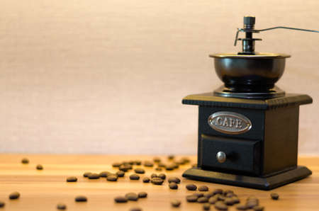 A coffee grinder with an open drawer and messy coffee beans on a wood table.