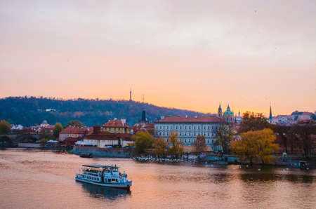 Dramatic sundown in the Vltava River with a boat passing by and a gradient of orange to pink colors reflecting from the sky into the water.
