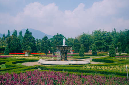 Bogor, Indonesia - A view of the flower themed park Taman Bunga Nusantara in a cloudy afternoon with a view to a water fountain centered in the picture. Stock Photo