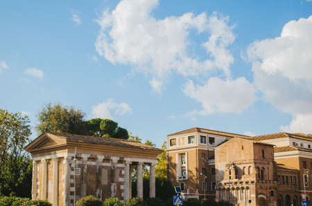 Rome, Italy - The ancient roman Temple of Portunus blended in the modern italian city of Rome during the afternoon with clouds in the blue sky.