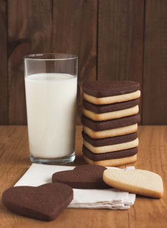 Glass of milk and heart shaped cookies on wood. Standard-Bild