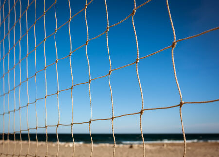 Closeup of beach volleyball net at sunset photo