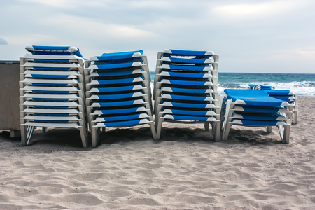 loungers: Stack of blue loungers on the beach Stock Photo