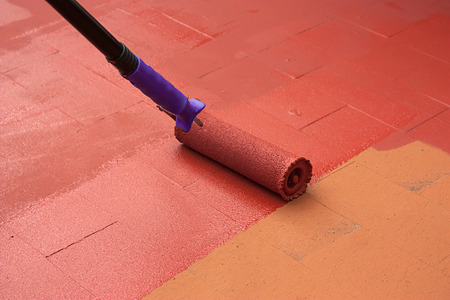 decks: Contract painter painting a floor on color red for waterproofing. He is using a paint roller.
