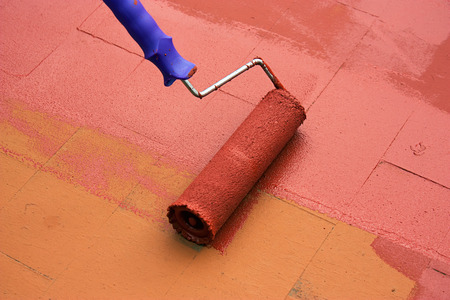Contract painter painting a floor on color red for waterproofing.