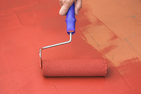 Hand painting a red floor with a paint roller for waterproofing