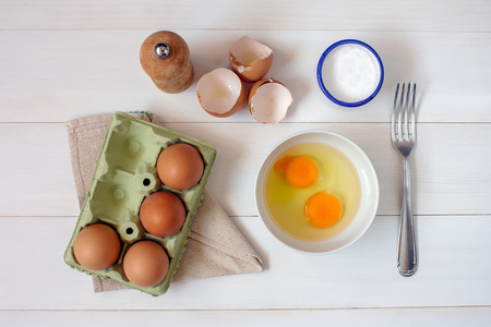 Fork for whipping eggs and raw eggs in a bowl on a white wooden table photo