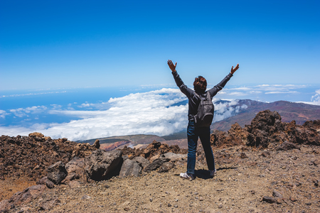 elated: Happy woman cheering elated with her arms raised up in the blue sky after hiking to volcano summit above the clouds. Tenerife. Stock Photo