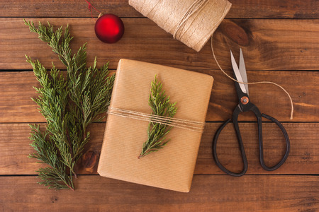 wrappings: Hand crafted gift on rustic wooden background with Christmas decoration.
