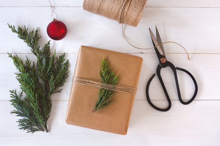 diy: Hand crafted gift on white wooden background with Christmas decoration.